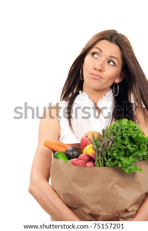 Happy young woman holding a shopping bag full of vegetarian groceries, mango, salad, asparagus, radish, avocado, lemon, carrots, oranges and thinking  isolated on white background - stock photo