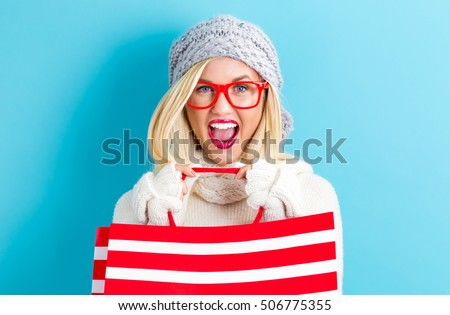 Happy young woman holding a shopping bag on a blue background