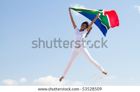 happy young woman holding a south african flag and jumping on beach - stock photo
