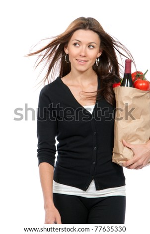 Happy young woman holding a supermarket paper shopping bag full of groceries - stock photo