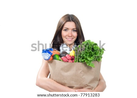 Happy young woman holding a supermarket shopping bag full of groceries, cucumbers, salad, asparagus, radish, avocado, lemon, carrots on white background - stock photo