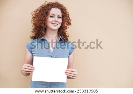 Happy young woman holding a white banner - stock photo