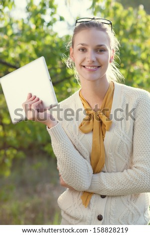 Happy young woman holding an ipad outdoors - stock photo