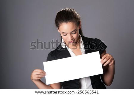 Happy young woman holding blank card - space for text, on grey background - stock photo