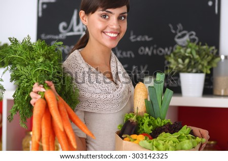 Happy young woman holding bunch of carrots in kitchen - stock photo
