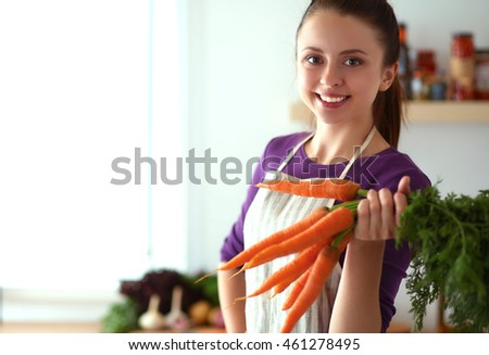 Happy young woman holding bunch of carrots in kitchen