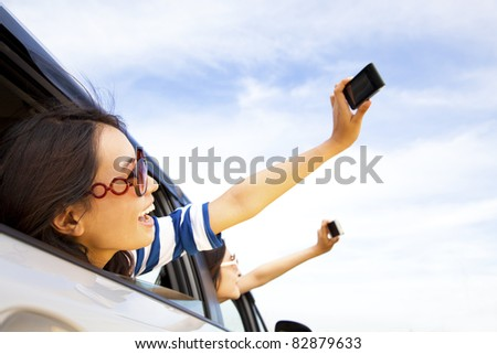 happy young woman  holding camera and mobile phone taking photos in the car - stock photo