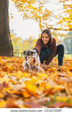 Happy young woman holding cheerful dog outdoors in autumn - stock photo