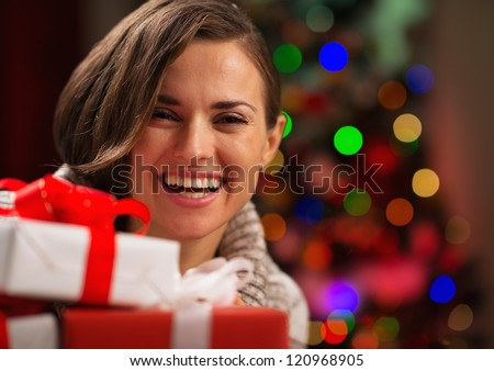 Happy young woman holding Christmas gift boxes - stock photo