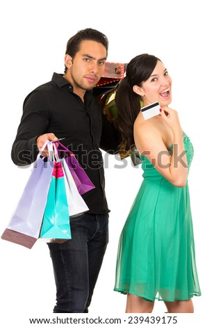 happy young woman holding credit card while boyfriend husband carries shopping bags isolated on white - stock photo