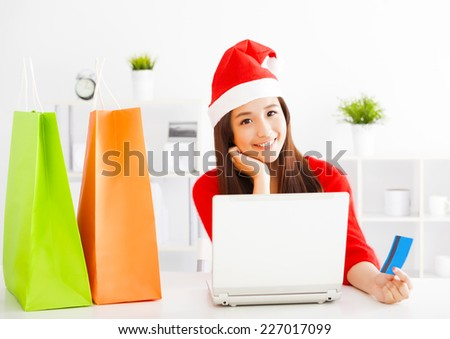 happy young woman holding credit card with tablet . Christmas shopping concept. - stock photo