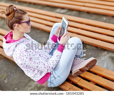 Happy Young Woman Holding Digital Tablet and Smiling - stock photo