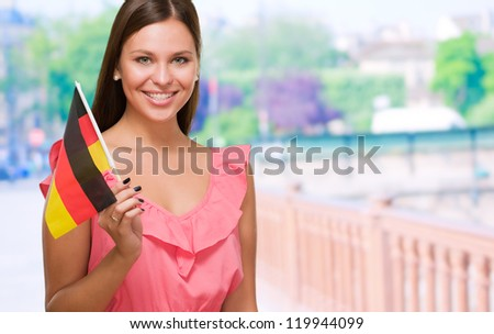 Happy Young Woman Holding German Flag against a street background - stock photo
