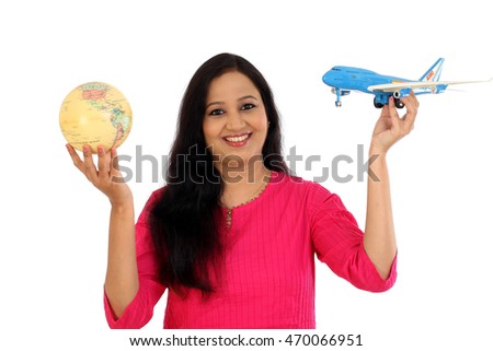 Happy young woman holding globe and toy plane against white background