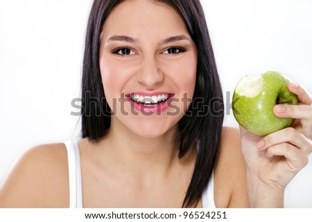 Happy young woman holding green apple with missing bite - stock photo