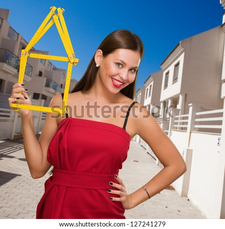 Happy Young Woman Holding House Frame outside - stock photo