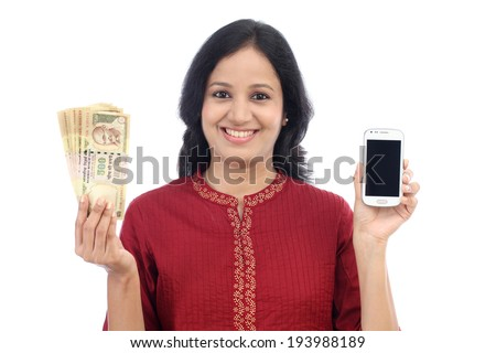 Happy young woman holding Indian currency and mobile phone against white - Mobile banking - stock photo