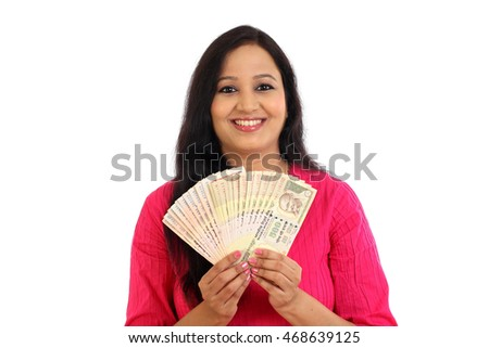 Happy young woman holding Indian rupee bank notes