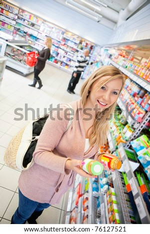 Happy young woman holding jar in the supermarket with people in the background - stock photo