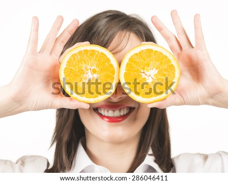 Happy young woman holding orange slices in front of eyes, studio shot on white background. Healthy lifestyle concept.