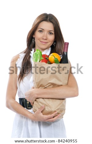 Happy young woman holding paper shopping bag full of groceries in supermarket, orange, salad, asparagus, bottle of red wine, tomatoes in hands on white background - stock photo