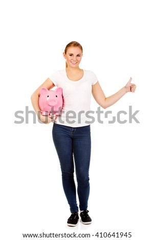 Happy young woman holding piggybank - stock photo