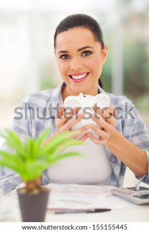 happy young woman holding piggybank and calculating savings - stock photo