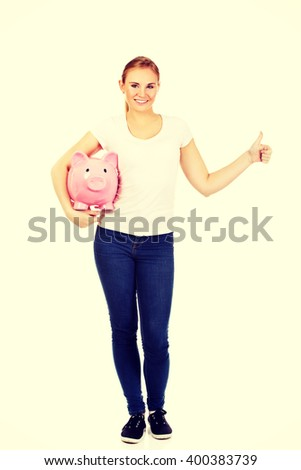 Happy young woman holding piggybank and showing thumb up - stock photo