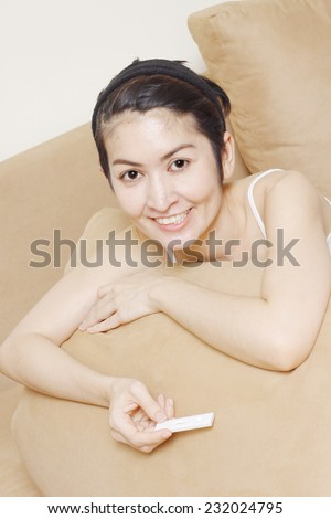 Happy young woman holding positive pregnancy test - stock photo