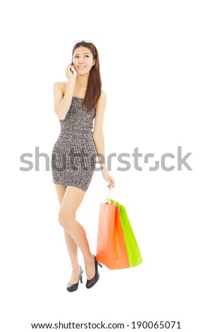 happy young  woman holding shopping bags and talking on the phone - stock photo