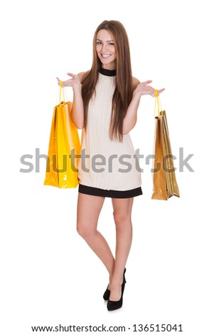 Happy Young Woman Holding Shopping Bags Over White Background