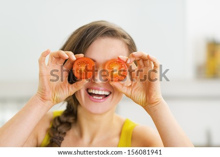 Happy young woman holding two slices of tomato in front of eyes