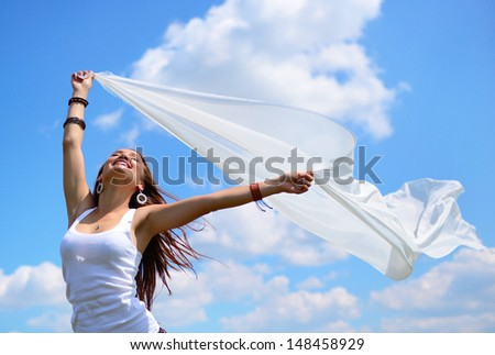 Happy young woman holding white scarf with opened arms expressing freedom, outdoor shot against blue sky - stock photo