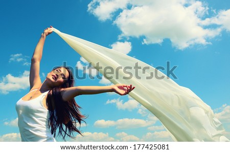 Happy young woman holding white scarf with opened arms expressing freedom, outdoor shot against blue sky, toned
