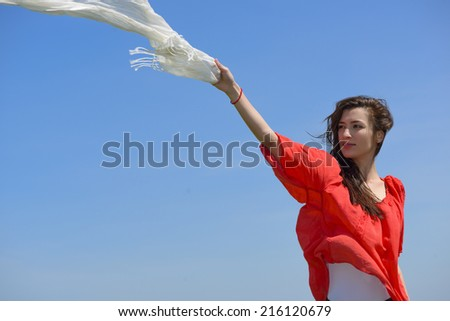 Happy young woman holding white scarf with opened arms expressing freedom, outdoor shot against blue sky. Beauty Girl Outdoors enjoying nature.
