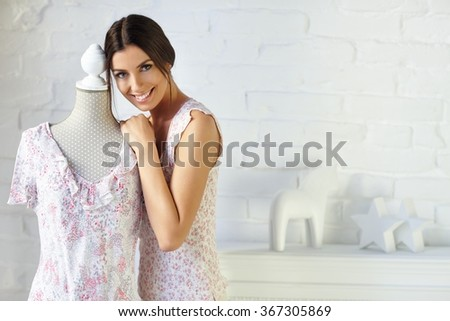 Happy young woman hugging dress-stand with blouse, smiling, looking at camera. - stock photo