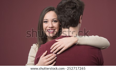 Happy young woman hugging her boyfriend on red background - stock photo