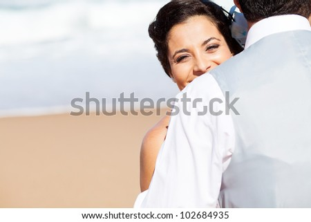 happy young woman hugging husband on beach - stock photo