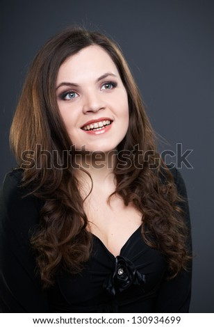 Happy young woman in a black dress. On a gray background