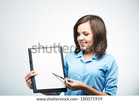 Happy young woman in a blue blouse. Holds a poster and points on it with a pen. On a gray background - stock photo