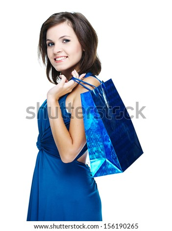 Happy young woman in a blue dress. Holds a gift bag. Isolated on white background