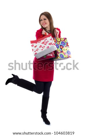 Happy young woman in a red dress with shopping bags isolated on white background