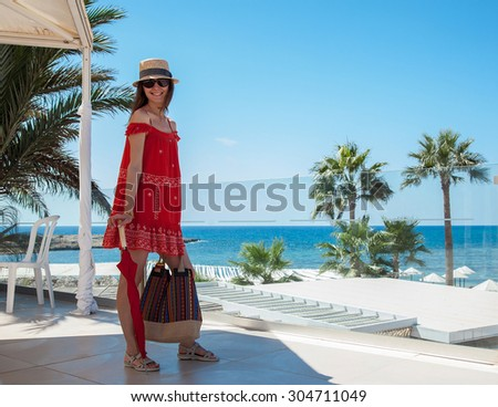 Happy young woman in a red sundress holding  a bag and an umbrella on seafront background - stock photo
