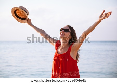 Happy young woman in a red sundress rejoices at summer vacation - stock photo