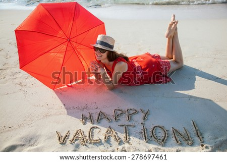 Happy young woman in a red sundress resting on a sandy beach - stock photo
