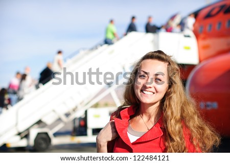 happy young woman in airport near the airplane - stock photo