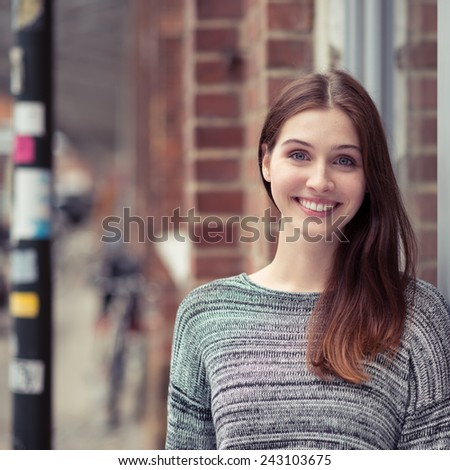 Happy young woman in an urban street standing outside a brick building looking at the camera with a charming smile - stock photo