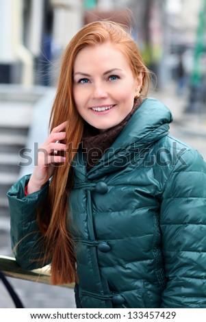 Happy young woman in autumn city