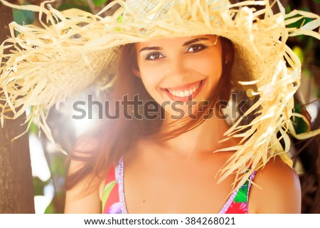 Happy young woman  in bikini and big hat drink juice through a straw. - stock photo