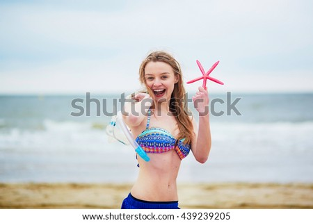 Happy young woman in bikini with snorkelling equipment and pink starfish enjoying summer vacation holidays by ocean or sea. Beach, travelling and people concept - stock photo